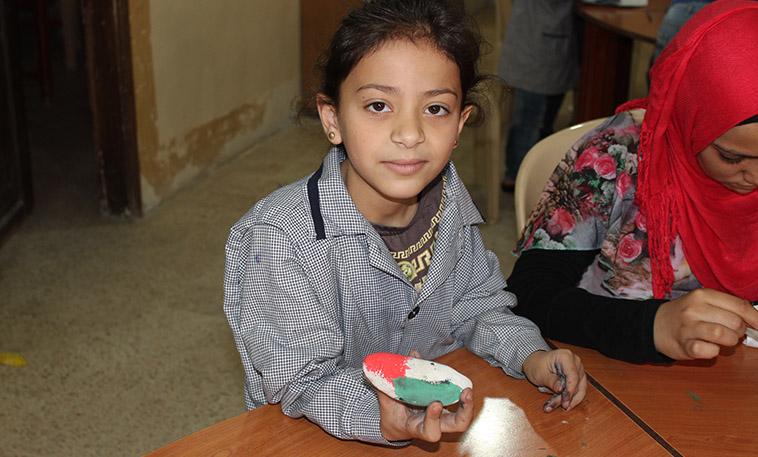 Petite fille palestinienne réfugiée au Liban peignant sur une pierre lors d'une activité artistique financée par l'OFCI