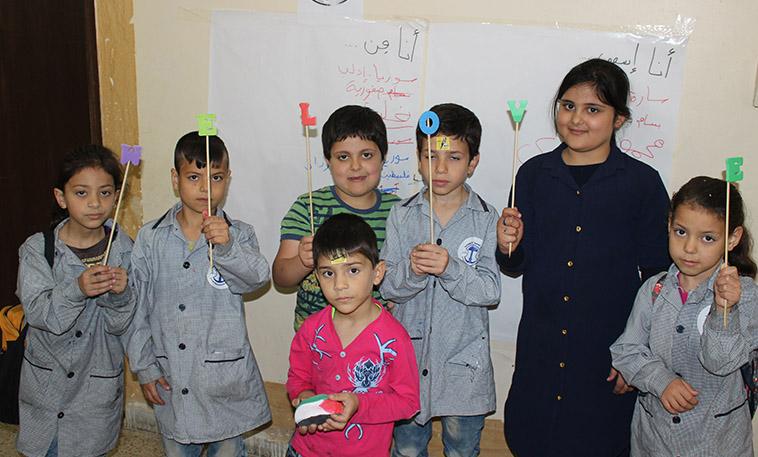 enfants palestiniens réfugiés participant à une activité artistique financé par l'OFCI. Ils tiennent des lettres formant We Love